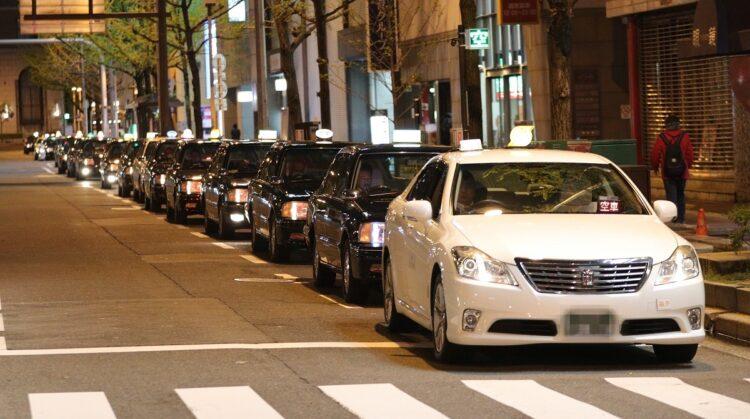 2020年春、新型コロナウイルス感染拡大の影響で閑散とした歓楽街では客待ちのタクシーが行列を作っていた(時事通信フォト)