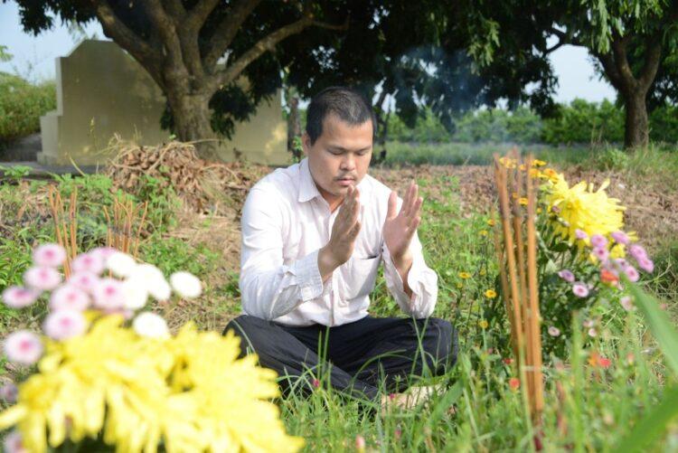 ベトナムにあるリンちゃんのお墓で祈りを捧げるハオさん。場所は首都ハノイから車で1時間半のフンイエン省で、筆者が2019年8月に撮影。