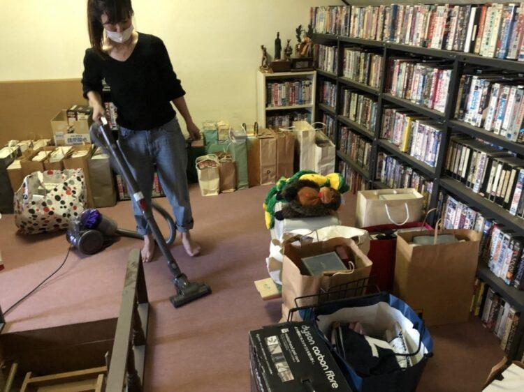 志村さんの自宅で掃除をする星野さん。棚にはビデオやDVDが並ぶ