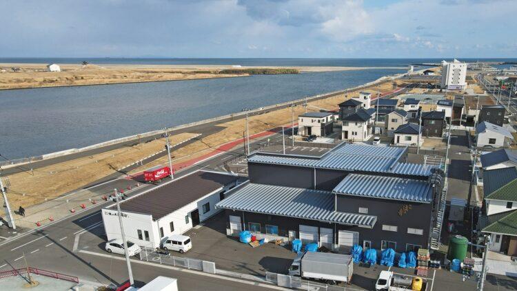 創業の地で復興(手前白と黒の建物)。目の前を名取川が流れ、右奥河口の先に太平洋が広がる