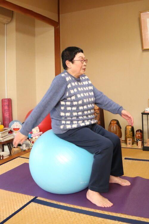 自宅でバランスボールを使って運動する橋田さん(2014年11月)