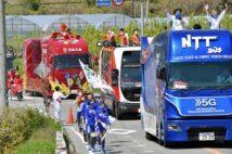 大音量のスポンサー車が大勢のスタッフを連れ行進。次走を務める聖火ランナーは手持ち無沙汰に車列を見送っていた