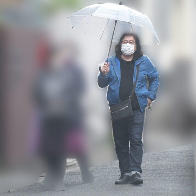 傘をさす高内氏