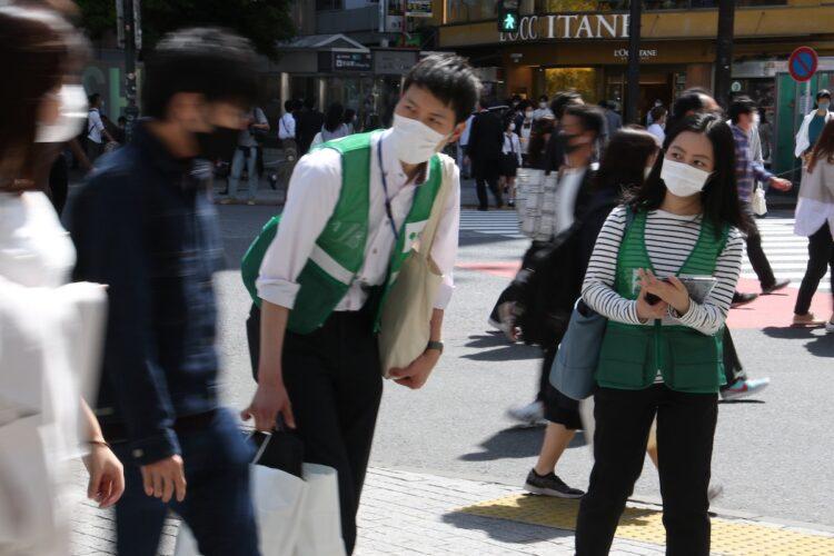 緊急事態宣言下、都の職員に外出の理由を尋ねられる若者たち(時事通信フォト)