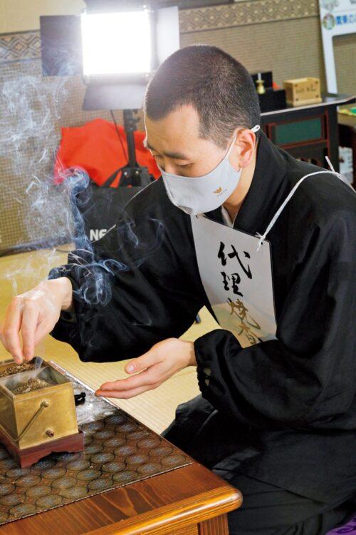 参列者がいない法要の場合は、僧侶が代理で焼香を行なう。画面の中で参列者が手を合わせる