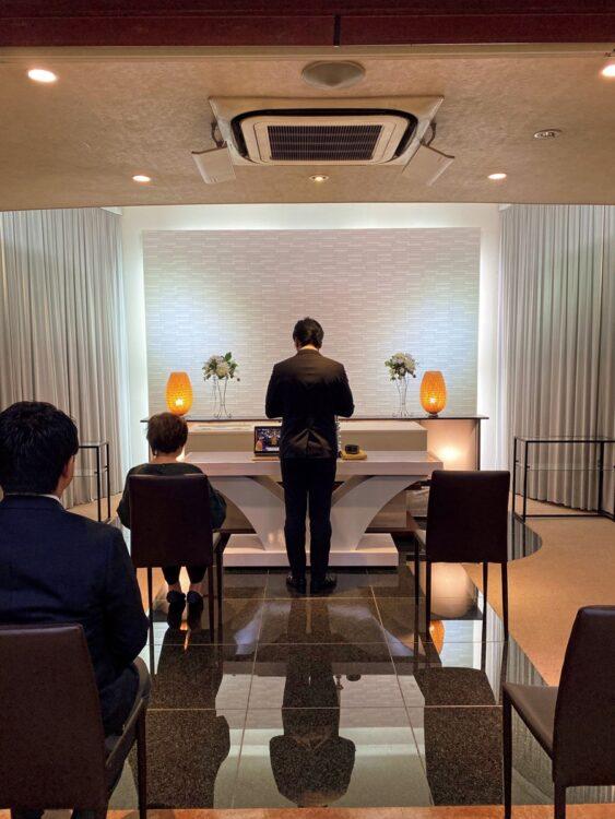 葬儀の動画が流れる画面に向かって参列者が焼香し手を合わせる。遺族の参加する葬式に、別会場で他の参列者が参加する