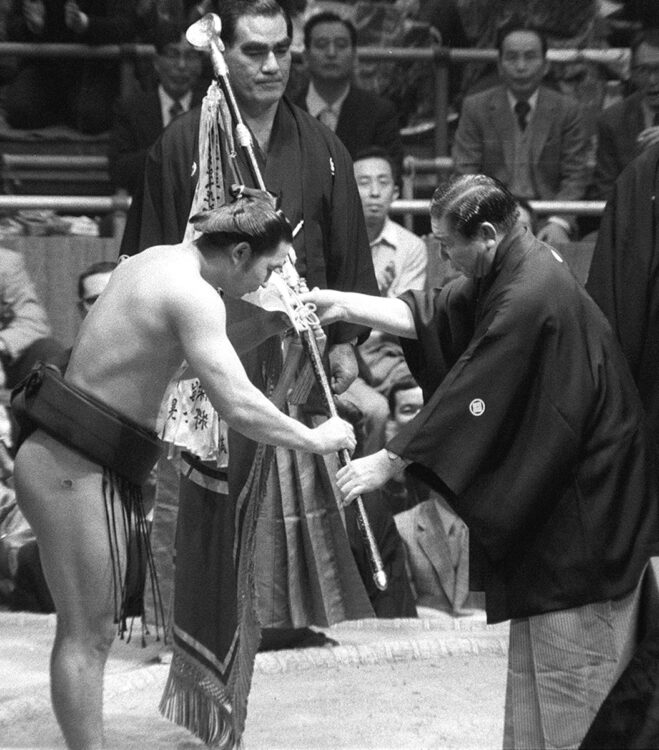 1975年、兄で師匠の二子山親方から優勝旗を受けた(写真/共同通信社)