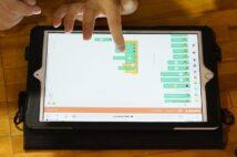 2020年度から必修化されたプログラミングをする小学生。操作に使うのはタブレット(イメージ、時事通信フォト)