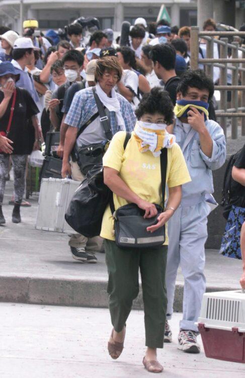 2000年の三宅島噴火で火山灰対策をして避難する住民(時事通信フォト)