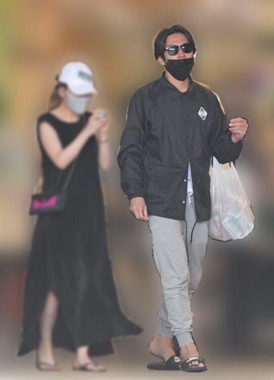 スーパーの大きな買い物袋を持つデート中の袴田吉彦