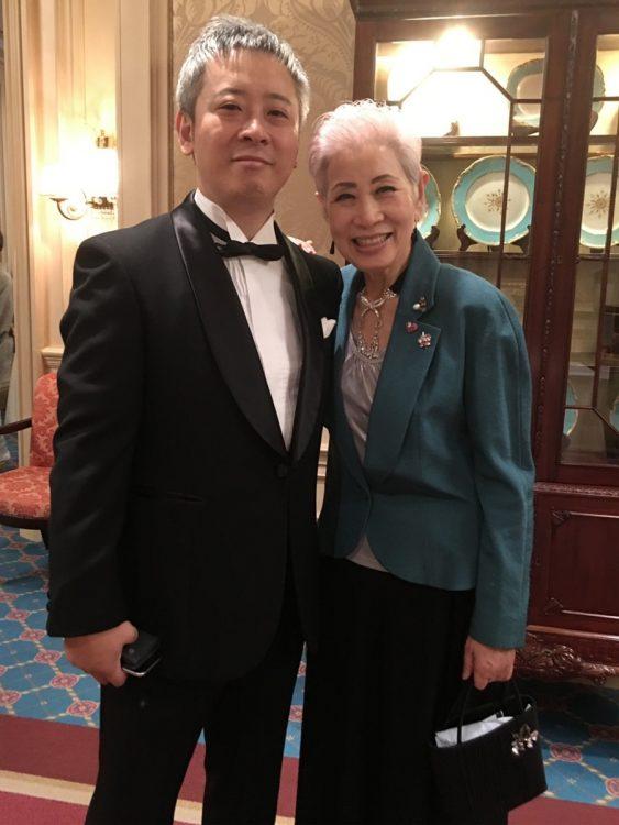 「チズコーポレーション」代表取締役の佳之さん(写真左)はチズさんの実弟の息子に当たる。IT関連企業で役員を務めた後、チズさんより「佐伯を名乗り、会社を継いでほしい」と言われ、2017年に養子縁組をして息子に。7月にはチズさんの夢だったサロンを日本橋・茅場町(東京)にオープンする予定。写真は2019年3月、チズさんと一緒に参加した、ガラパーティの式典で撮影したもの