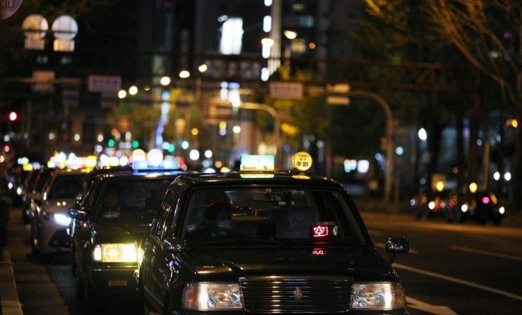 新型コロナウイルス感染拡大の影響で閑散とした歓楽街で行列を作る客待ちのタクシー(イメージ、時事通信フォト)