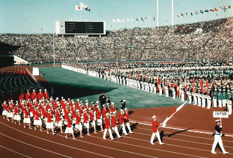 1964年、東京五輪。94か国が参加した前回東京大会の開会式。前日までの雨があがり抜けるような青空のもと、日の丸カラーの355人が入場行進した(写真/共同通信社)