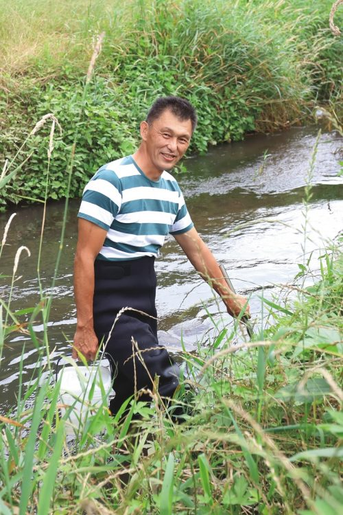 川に入って標本撮影に使う魚を網で捕獲する松沢陽士さん