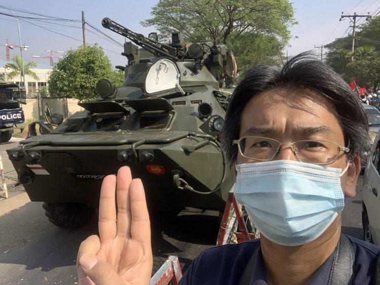 軍の装甲車の前で「3本指」を立ててクーデターに反対の意思表示をする北角さん (写真/北角裕樹さん提供)