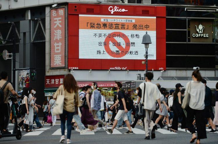 緊急事態宣言が発令される中、渋谷のスクランブル交差点を行き交う人々(イメージ、時事通信フォト)