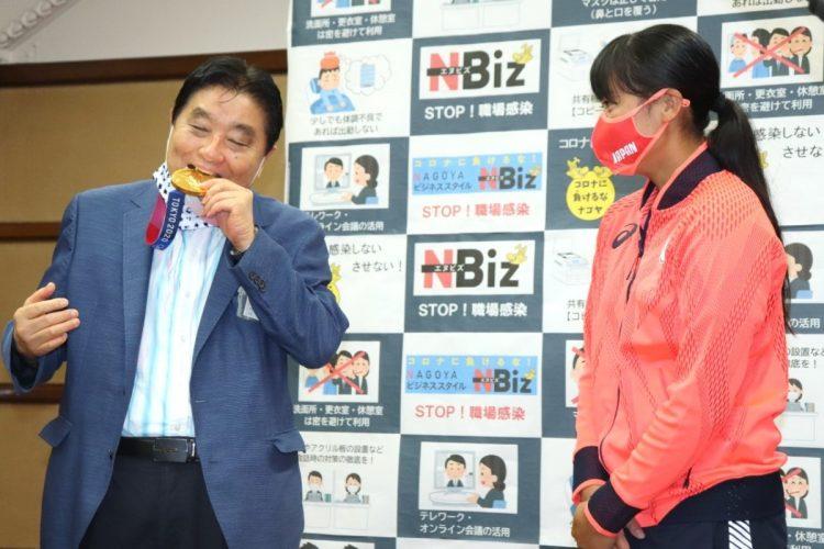 ソフトボール女子五輪代表の後藤希友投手(右)の表敬訪問を受け、首に掛けてもらった金メダルにかみつく名古屋市の河村たかし市長(時事通信フォト)