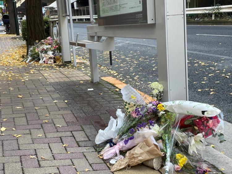 路上生活者の女性が亡くなったバス停に供えられた花束。東京都渋谷区(時事通信フォト)