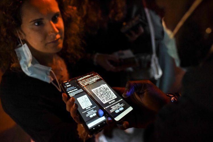 ナイトクラブの入り口でワクチンパスポートを見せる女性(写真/フランス西部、時事通信社)