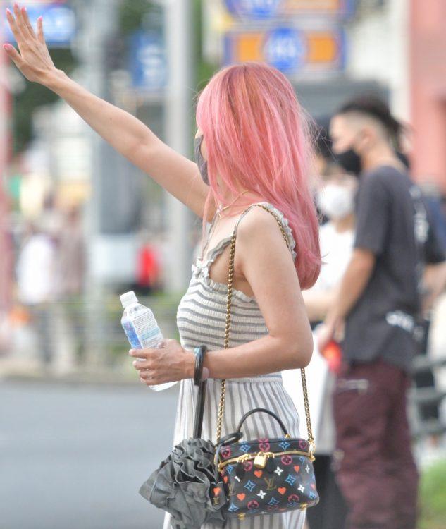 ピンクの髪をなびかせて手を挙げる