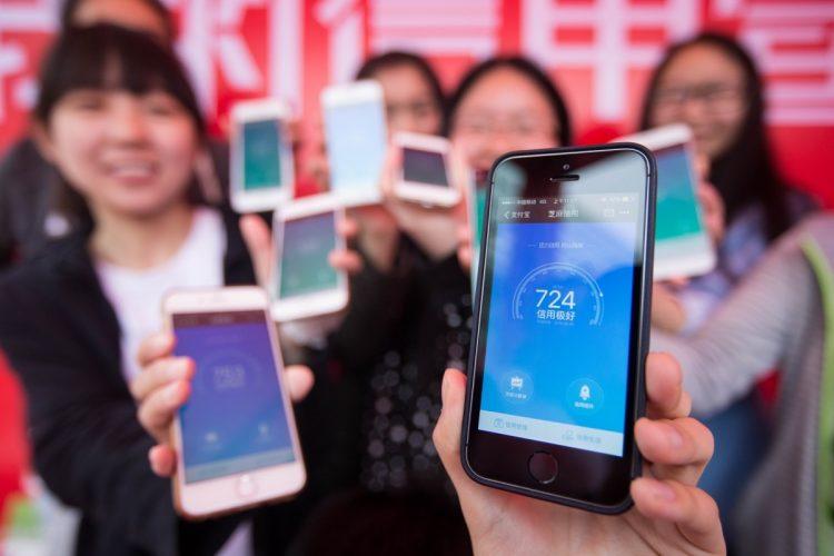 スマホに表示される自分の信用スコアを見せる中国の女性たち。700点以上は「極めて良い」(Imaginechina/時事通信フォト)