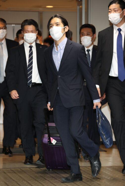 成田空港では、要人警護のスーツ男性らが両脇を固めた