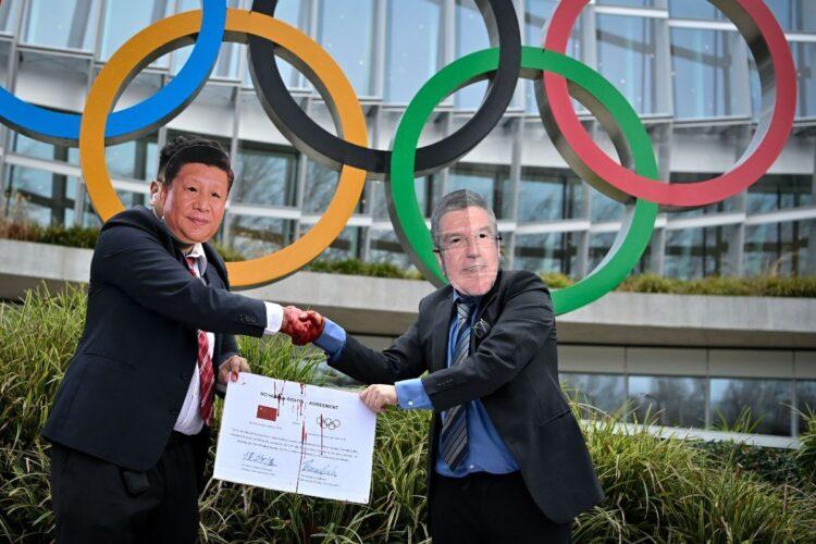 スイスで行われた北京五輪反対のパフォーマンス。習近平とトーマス・バッハIOC会長の「ガッチリ握手」は悪者感たっぷり(AFP=時事)